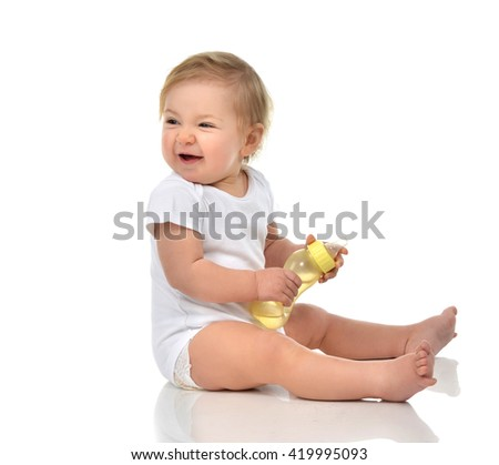 Infant child baby toddler sitting and drinking water from the feeding bottle isolated on a white background - stock photo