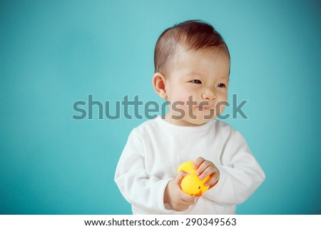 Infant child with rubber duck - stock photo