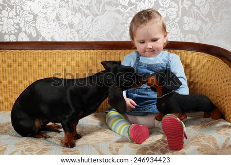 Infant girl sits on sofa and looks at black basset dog playing with it's toy replica - stock photo