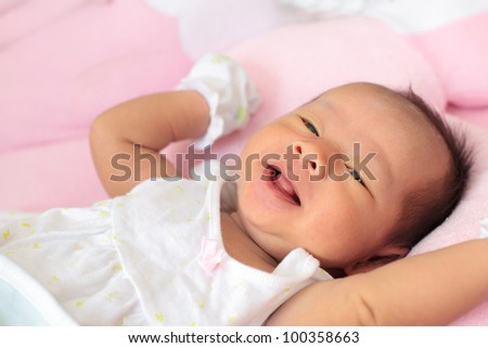 infant sleep on the bed and smiling - stock photo