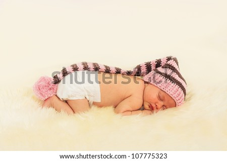 infant sleeping in the white sheep's clothing. - stock photo