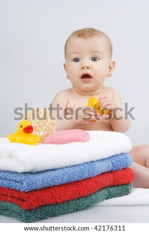 Infant with towels,with soap,quack - quack,on whites background. - stock photo