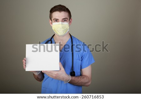 Infection Prevention concept shot of a doctor in mask and gloves holding up a sign with room for your own copy. - stock photo