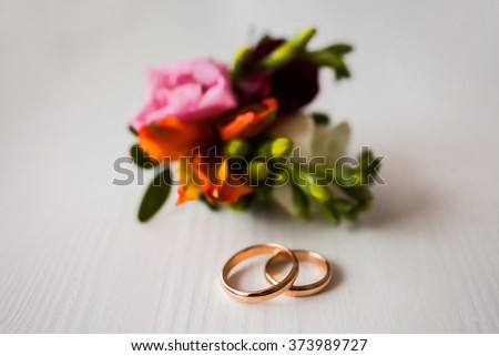 infinity sign of the rings, wedding rings on a white background,wedding bands, wedding jewelry, wedding preparation, pink boutonniere, wedding rings flowers, wedding rings on white, rings and flowers  - stock photo