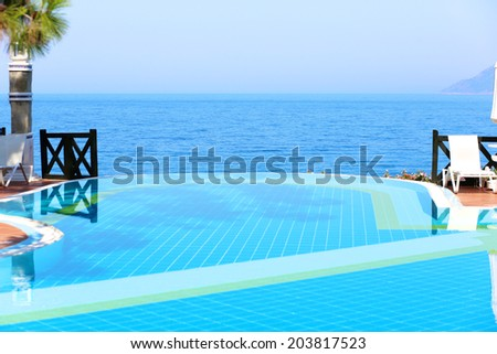 Infinity swimming pool with beautiful view on Aegean Sea at the luxury hotel, Turkey  - stock photo