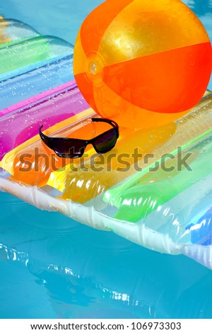 Inflatable mattresses, sunglasses and a ball in the pool. - stock photo