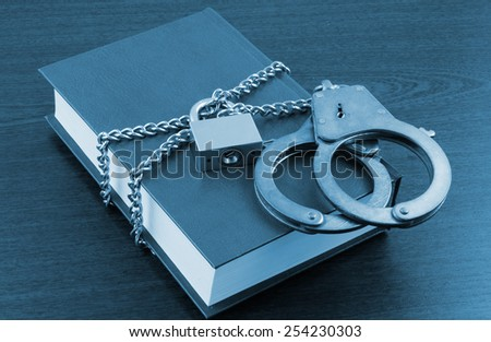 Information security concept, handcuffs, book with chain and padlock - stock photo