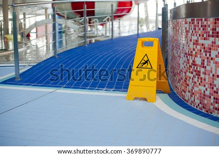 Information signs indicating the slippery floor when exiting the pool (Shallow DOF). - stock photo