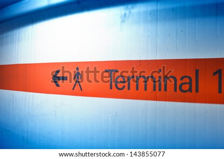 Informational sign on red stripe showing terminal number (one) at international airport - stock photo