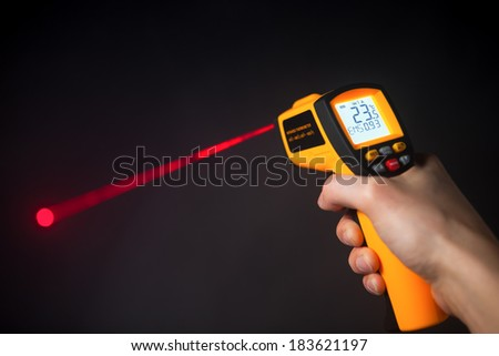 infrared laser thermometer in hand - stock photo