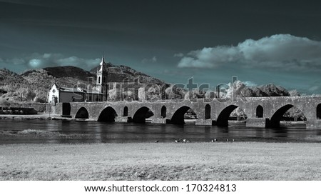Infrared medieval bridge and church of Ponte de Lima, north of Portugal - stock photo