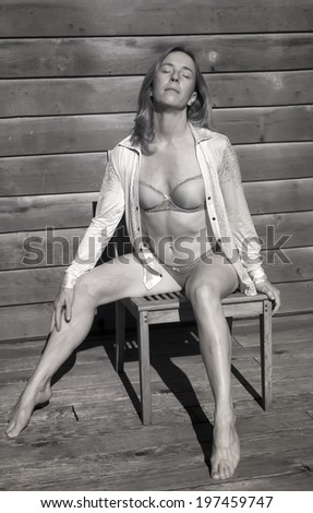 Infrared portrait of a beautiful woman in her bra and panties sitting in the sun. - stock photo