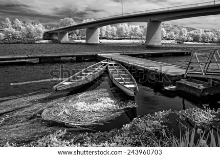 Infrared river boats, wooden pier an new bridge from Ponte de Lima, Lima river, north of Portugal - stock photo