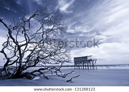 infrared shot of house on stilts standing alone after storm - stock photo