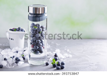 Infused water with mint and blueberries in a bottle - stock photo