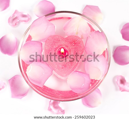 Infused water with rose petals in a reflection bowl - stock photo