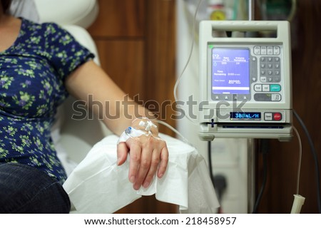 Infusion pump feeding IV drip into patients arm focus on needle - stock photo