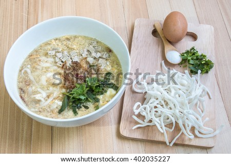 Ingredient of Pho and bowl of Vietnamese noodle, original powder noodle, egg, and thai parsley put on chopping block - stock photo
