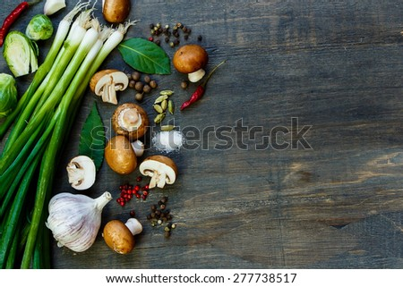Ingredients and fresh mushrooms on dark wooden table. Background with space for text. Vegetarian food, health or cooking concept. - stock photo