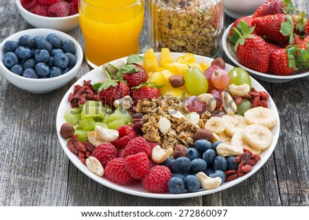 ingredients for a healthy breakfast - berries, fruit and muesli on wooden table, close-up - stock photo
