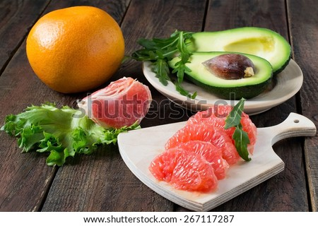 Ingredients for a healthy salad: avocado, grapefruit, arugula and lettuce on a wooden background. Selective focus - stock photo