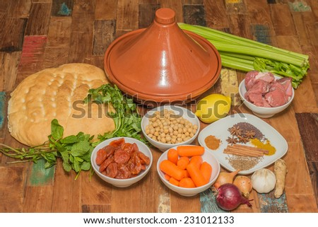 Ingredients for a Moroccan tagine dish with chick peas, lamb, carrots, celery, lemon, onion, cinnamon, star anise, bread - stock photo