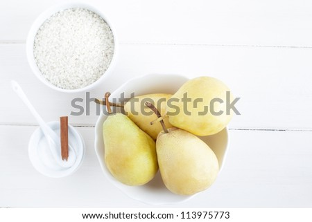 Ingredients for a rice pudding dessert: pears, rice pudding, sugar. - stock photo