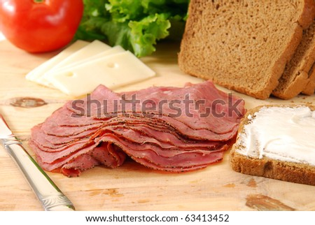 Ingredients for a roast beef sandwich laid out on a cutting board - stock photo