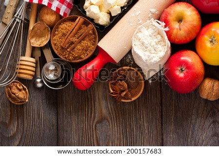 Ingredients for apple pie cooking. Fresh red apple, butter, flour, brown sugar, nuts and spices on a rustic wooden background. - stock photo