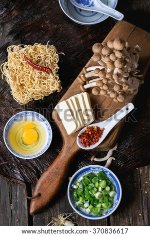 Ingredients for asian ramen soup. Noodles, spring onion, feta cheese, mushrooms, egg and chili pepper in asian porcelan bowls over old wooden table. Dark rustic style. Top view - stock photo