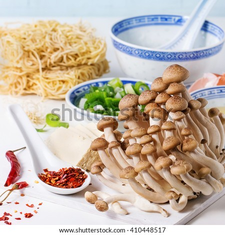 Ingredients for asian ramen soup. Noodles, spring onion, feta cheese, mushrooms, egg and chili pepper in asian porcelan bowls over white kitchen table. Square image with selective focus - stock photo
