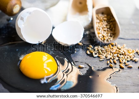 Ingredients for baking a bread, egg, wheat and flour on the dark cutting board - stock photo