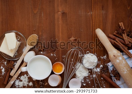 Ingredients for baking dough including flour, eggs, milk, butter, sugar, cinnamon, anise star, whisk and rolling pin on wooden rustic background, empty space for text, top view, toning - stock photo