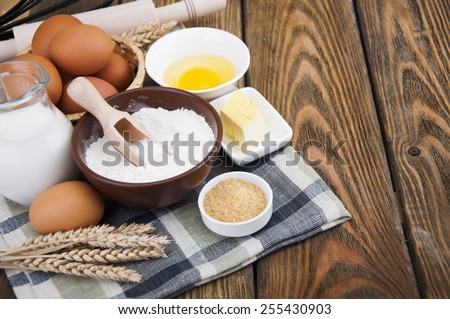 Ingredients for baking. Flour, eggs, butter, sugar, milk on wooden background - stock photo