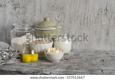 Ingredients for baking - flour, milk, butter, eggs on a light wooden table. Free space for text.  Food background - stock photo
