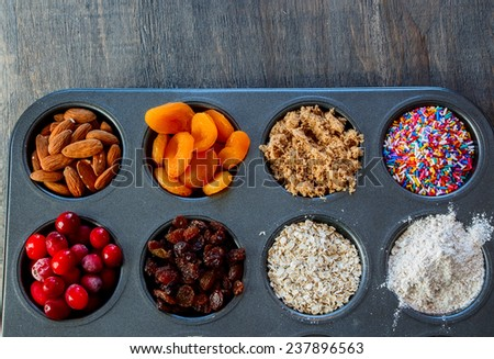 Ingredients for baking  in cupcake's forms on old wooden table. Top view. - stock photo