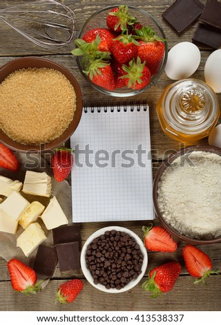 Ingredients for baking strawberries cake on a wooden background - stock photo