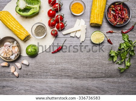 ingredients for burritos with tomato, pepper, spicy chili, corn, cheese and garlic border with space for text on grey wooden rustic background top view close up - stock photo