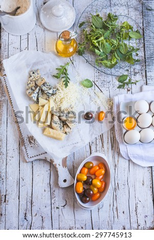 Ingredients for cook quiche serving on a kitchen rustic wooden white table. Ingredients include various cheese, blue cheese, egg, green leaves, tomato cherry. See series for recipe   - stock photo
