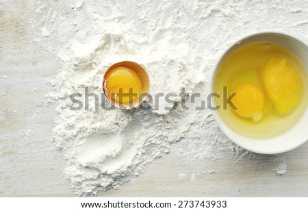 ingredients for cooking cream, baking,wheat flour, eggs, whisk,Ingredients for the dough with a broken egg - stock photo