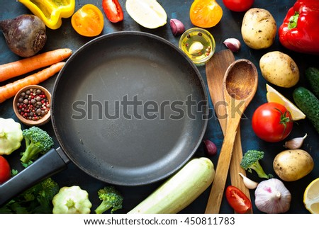 Ingredients for cooking. Fresh vegetables, frying pan and spices on dark table. Healthy food. - stock photo