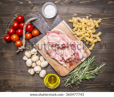 Ingredients for cooking fusilli pasta with bacon vegetables, spices and herbs on a cutting board on wooden rustic background top view  - stock photo