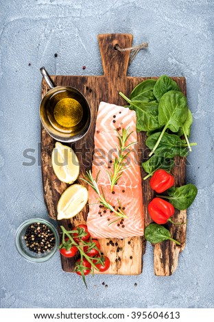 Ingredients for cooking healthy dinner. Raw salmon fillet, spinach, tomatoes, olive oil, lemon, peppers, rosemary and spices on a rustic wooden board over concrete textured grey background. Top view - stock photo