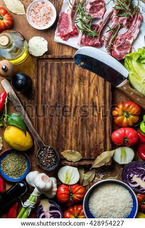 Ingredients for cooking healthy meat dinner. Raw uncooked lamb chops with vegetables, rice, herbs and spices over rustic wooden background, dark chopping board in center with copy space. Top view - stock photo