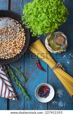 Ingredients for cooking italian pasta - olive oil, tomatoes, pine nuts, spice and herbs on old wooden table, mediterranean cuisine recipe - stock photo