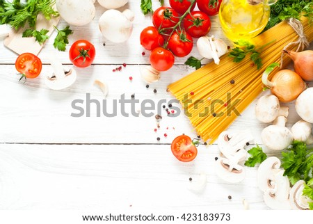 Ingredients for cooking Italian pasta - spaghetti, tomatoes, mushrooms  and greens at white. Top view with space for text. - stock photo