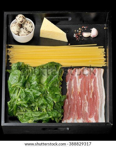 ingredients for cooking Italian style dishes spaghetti Carbonara. spaghetti, bacon, cheese, quail eggs, garlic, spices, Basil on a black tray. top view - stock photo