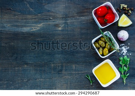 Ingredients for cooking (olive oil, tomatoes, garlic, olives, lemon, spices and herbs) on dark wooden background with space for text.Vegetarian food, health or cooking concept. - stock photo