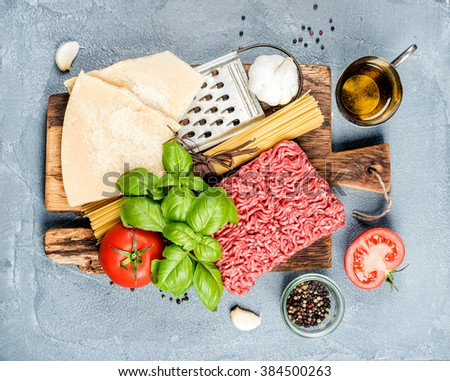 Ingredients for cooking pasta Bolognese. Spaghetti, Parmesan cheese,  tomatoes, metal grater, olive oil, garlic, minced meat and fresh basil on rustic wooden board over grey background, top view - stock photo