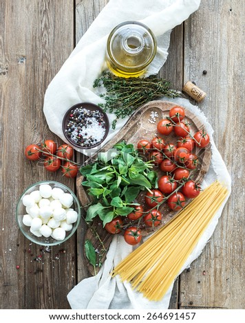Ingredients for cooking pasta. Spaghetti, basil, cherry-tomatoes, mozarella, olive oil, thyme, salt, spices on rustic chopping board over old wood background. Top view  - stock photo